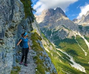 Hiker on the hiking trail through the imposing Brenta Dolomites