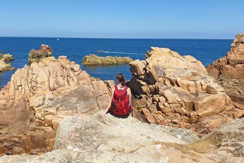 Wanderer genießt den tollen Ausblick auf die roten Granitfelsen und das Meer
