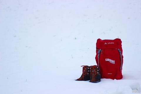 Wanderrucksack und Wanderschuhe im Schnee