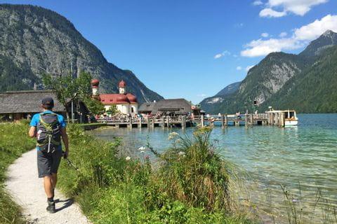 Hiker at Lake Koenigssee and church St. Bartholomae