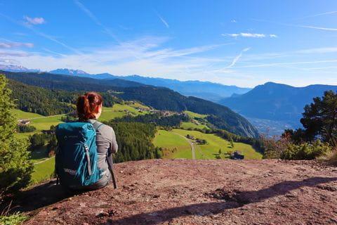 Sitzende Wanderin bestaunt die südtiroler Bergwelt