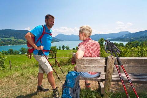 glückliche Wanderer genießen eine Rast, im Hintergrund der schöne Tegernsee