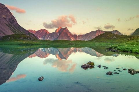 Wunderschöner Sonnenuntergang vom spiegelnden Bergsee in den Bergen