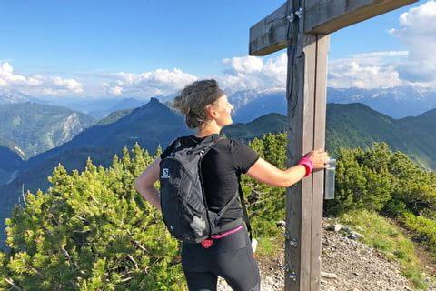Hiker at the summit cross in the Salzkammergut