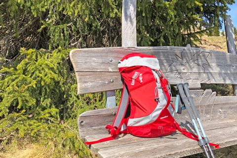 Red hiking backpack on hiking bench