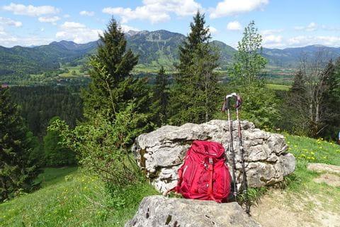 Wandern mit Rucksack und Wanderstöcken durch die Bayerische Berglandschaft