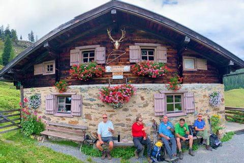 Herr Preusche mit Freunden vor einer urigen Berghütte