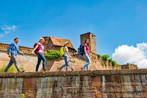 Wanderer wandern entlang der Burgmauer