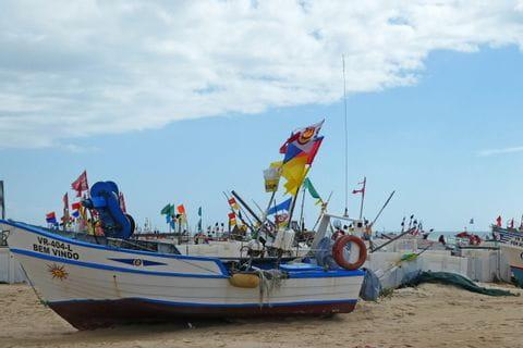 Buntes Fischerboot am Sandstrand der Algarve