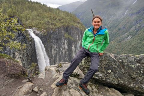 Hiker in Jotunheimen National Park, with mountains and waterfall in the background