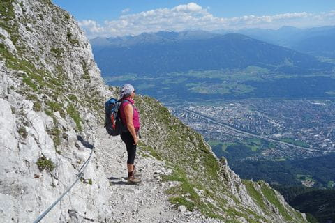 Hikers enjoy the stony hiking trail and the wonderful view down to Innsbruck