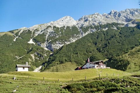 Hiking on the trans Tyrol with a view of the mountains and hut