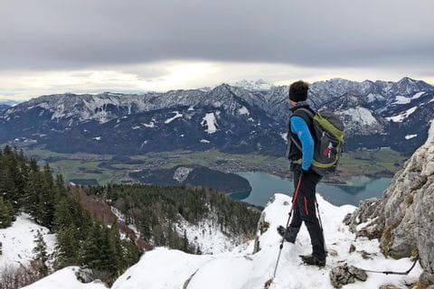 Wanderer am verschneiten Gipfel mit Blick auf den winterlichen Wolfgangsee