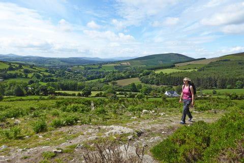Wanderin bestaunt die waunderbar grüne Landschaft Irlands