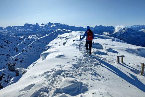 Wanderer am Berggipfel in winterlicher Landschaft