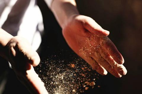 Hände mit Mehl beim Brot backen