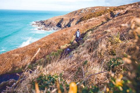 Walker on the coastal path in Cornwall