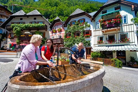 Group of hikers at the fountain of village Hallstatt