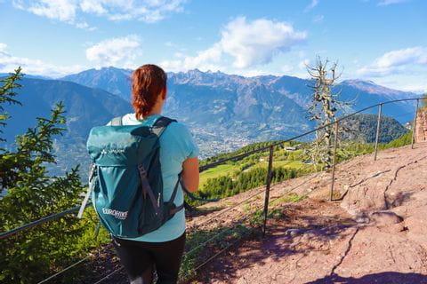 Wanderin genießt den Ausblick auf Meran und die südtiroler Bergwelt
