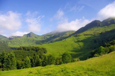 Wiesenfelder und Bergkulisse beim Wandern am Puy Saint